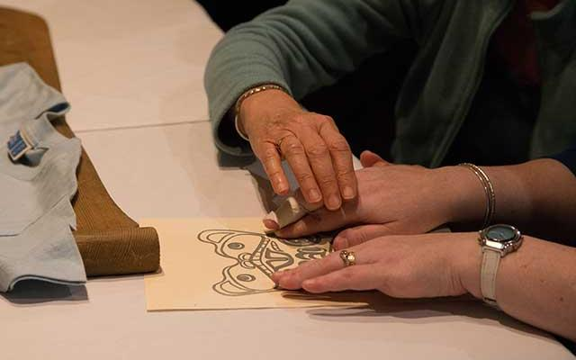 Visitor engaging with art using swirl paper
