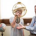 Staff showing student an astrolabe
