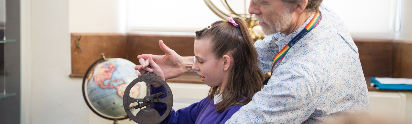 Staff showing student how to use astrolabe