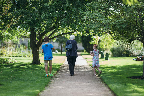 Two children and grandparent walking in botanic garden