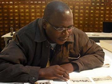 Student historian Pius Cokumu looking at Luo photographs, Kenya at the Pitt Rivers Museum